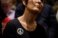 A woman wearing a button with a peace sign that says &quot;Ron Paul for Peace&quot; listens as congressman Ron Paul speaks at a town hall meeting and rally at the Church Landing at Mills Falls hotel in Meredith, New Hampshire, on Jan. 8, 2012. Paul is seeking the 2012 Republican presidential nomination.