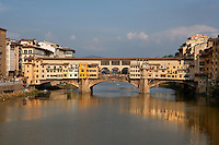 General view of the Ponte Vecchio, Florence, Tuscany, Italy, pictured on June 10, 2007, in the afternoon. The Ponte Vecchio, or Old Bridge, crosses the River Arno at its narrowest point. The original bridge, possibly Roman and first documented in 999, was swept away in a flood in 1117, rebuilt, swept away again in 1333 and rebuilt in 1345. In 1565 Cosimo de Medici commissioned Vasari to design a corridor, above the famous shops along the bridge, connecting the Palazzo Vecchio to the Pitti Palace. In 1593 the Medicis prohibited butchers, the traditional occupants, from the shops which were soon taken by Goldsmiths. Florence, capital of Tuscany, is world famous for its Renaissance art and architecture. Its historical centre was declared a UNESCO World Heritage Site in 1982. Picture by Manuel Cohen.
