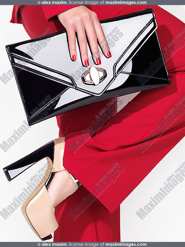 Fashion product shot of a lady wearing a red suit and high heel platform shoes holding a clutch handbag