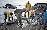Workers attempt to clean sand and rocks along the shoreline in Botongon, a neighborhood of Estancia, Philippines, in an effort to remove oil that spilled there when Typhoon Haiyan swept through the area in November 2013. The storm was known locally as Yolanda. Most residents who lived along the affected coastline remain camped in temporary shelters elsewhere, despite government efforts to get many to return. The ACT Alliance is accompanying them as they struggle to survive.