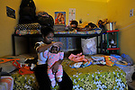 An Eritrean woman holds her baby as she watches TV, sitting at her room in a compound of Eritrean asylum-seekers in southern Tel Aviv, Israel.
