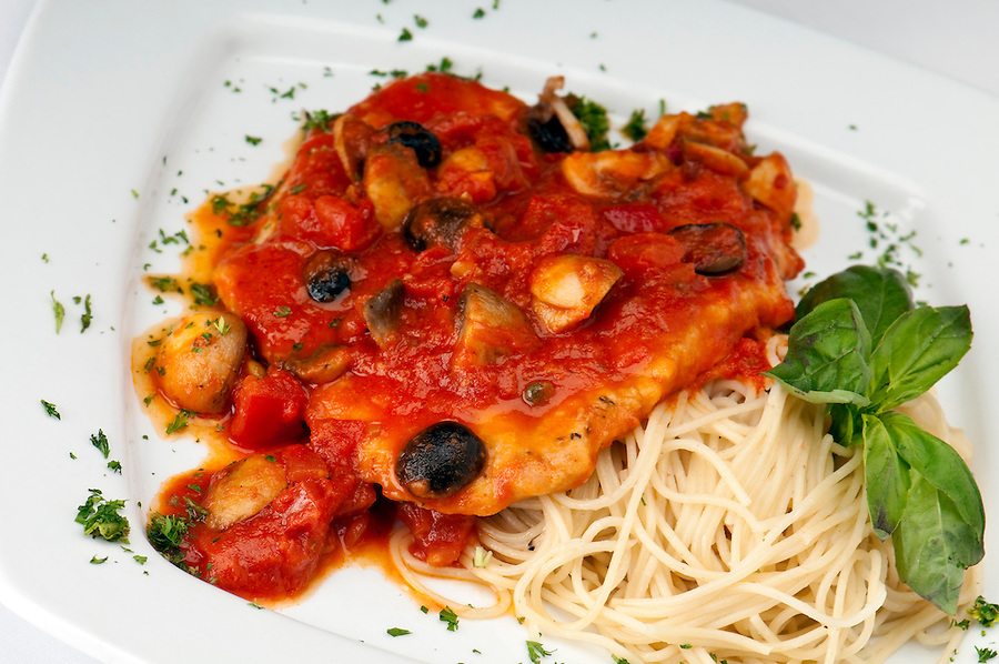 Plate of chicken pizzaiola, with fresh tomatoes, sweet onions, mushrooms with a hint of rose wine over a bed of spaghetti.