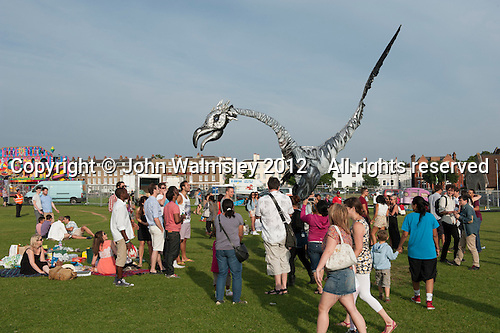 """Dynosaurs (saurus) walking amongst the crowd at """"Showtime"""", part of the London 2012 Festival of Arts to celebrate the London Olympics.  A family fun spectacle including dance, painting, music, acrobatics and some large mobile dynosaurs walking amongst the crowd.  On Blackheath Common, Saturday August 4th and funded by the Mayor of London and Arts Council England."""
