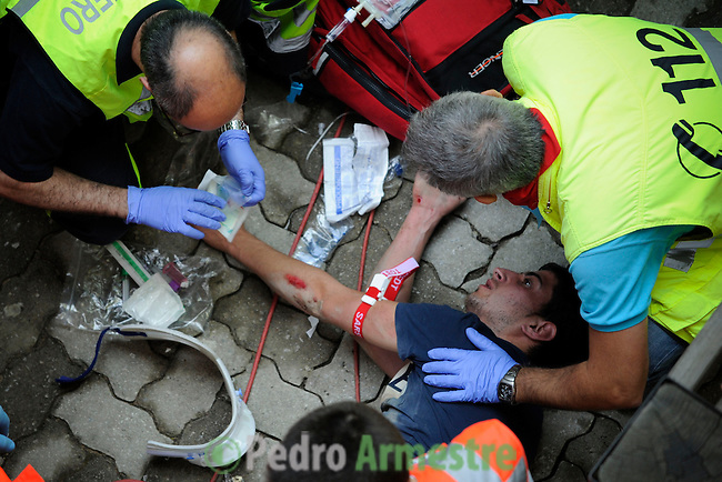 The red Cross workers attend a runner during during the bull run of the San Fermin Festival, on July 9, 2013, in Pamplona, northern Spain. (c) Pedro ARMESTRE