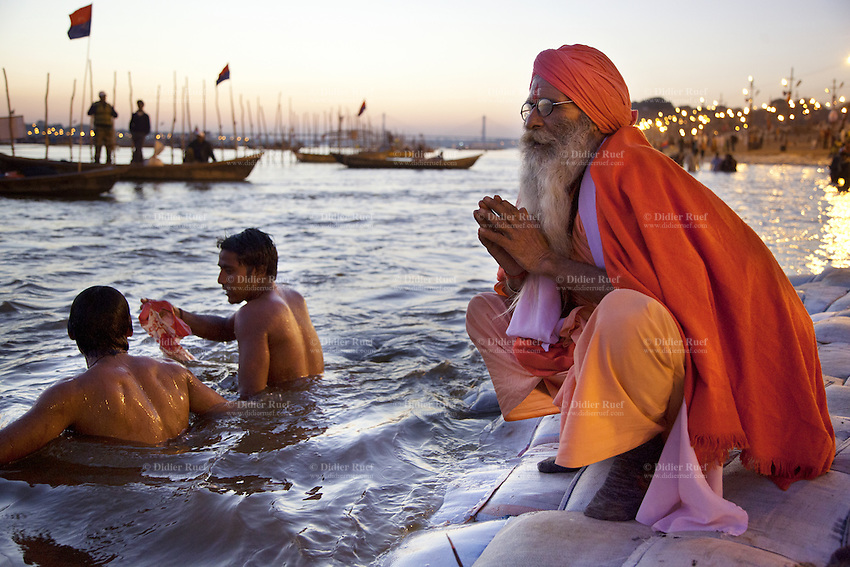 India. Uttar Pradesh state. Allahabad. Maha Kumbh Mela. Two Indian Hindu devotees take a holy dip and a sanyasi prays in Sangam at the sunset. The old saint man wears saffron clothes. Sanyasis, or renunciates, have left behind all material attachments. They are renouncers who have chosen to live a life apart from or on the edges of society in order to focus on their own spiritual practice. The Kumbh Mela, believed to be the largest religious gathering is held every 12 years on the banks of the 'Sangam'- the confluence of the holy rivers Ganga, Yamuna and the mythical Saraswati. In 2013, it is estimated that nearly 80 million devotees took a bath in the water of the holy river Ganges. The belief is that bathing and taking a holy dip will wash and free one from all the past sins, get salvation and paves the way for Moksha (meaning liberation from the cycle of Life, Death and Rebirth). Bathing in the holy waters of Ganga is believed to be most auspicious at the time of Kumbh Mela, because the water is charged with positive healing effects and enhanced with electromagnetic radiations of the Sun, Moon and Jupiter. The Maha (great) Kumbh Mela, which comes after 12 Purna Kumbh Mela, or 144 years, is always held at Allahabad. Uttar Pradesh (abbreviated U.P.) is a state located in northern India. 7.02.13 © 2013 Didier Ruef