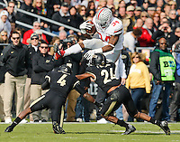 Ohio State Buckeyes running back Carlos Hyde (34) leaps over Purdue Boilermakers safety Taylor Richards (4) and defensive back Frankie Williams (24) during the first quarter of the NCAA football game at Ross-Ade Stadium in West Lafayette, Ind. on Nov. 2, 2013. (Adam Cairns / The Columbus Dispatch)
