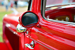 The sideview mirror area is a closeup of of a red 1934 Ford 2-door sedan at the Antique Auto Show, where New York Antique Auto Club members exhibited their cars on the farmhouse grounds of Queens County Farm Museum. Its owner, Dennis Kusold of Franklin Square, explained the car has its original steel body and frame.