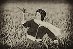 A young boy dreaming of becoming a pilot runs through a wheat field with a model aircraft.