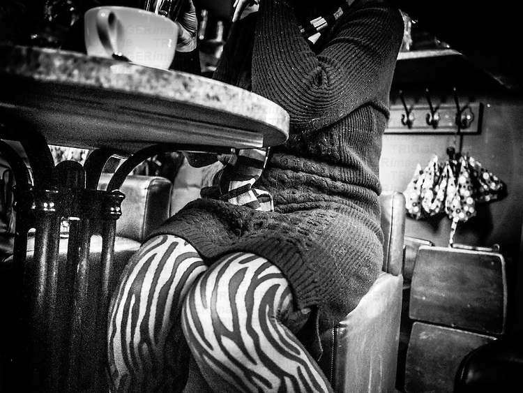 Voyeuristic view of a woman's legs under a cafe table