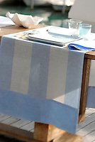 A pale blue and white runner is used as a place setting on an outdoor dining table