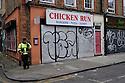 London, UK. 04.04.2015. Man on his phone outside Chicken Run shop, East London. Photograph © Jane Hobson.