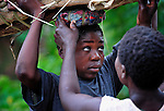 "A woman gets help setting a load of firewood on her head in Chidyamanga, a village in southern Malawi that has been hard hit by drought in recent years, leading to chronic food insecurity, especially during the ""hunger season,"" when farmers are waiting for the harvest."