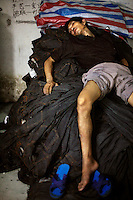 A factory worker takes a break at dawn on a pile of jeans after working all night using a sanding machine at a garment factory. The factory, which specifically carries out a wear-and-tear process used to achieve a fashionable distressed look, produces approximately 10,000 pairs of jeans every day. Thousands of workers labour through the night scrubbing, spraying and tearing jeans in order to meet the production demand. The factory is owned by Huang Dehong, who left his impoverished village and arrived penniless in Zhongshan twenty years ago. China, the &quot;factory of the world&quot;, is now one of the world's largest producers of jeans and its textile workers are among the 200 million migrant labourers criss-crossing the country looking for a better life.