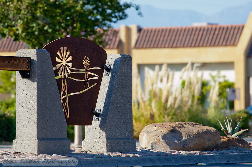 "Iron plates with windmill cutouts play a key part of the Grand Avenue Beautification Project.  This one is backlit by a late afternoon sun illuminating trees, rocks, and pampas grass.  This was part of the 2015 rebuild of the Grand Avenue and Diamond Bar Boulevard intersection for Diamond Bar's 2015 ""Grand Avenue Beautification"" project, landscape architecture for the project was by David Volz Design."