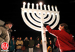 """Southbury, CT- 08, December 2010-120810CM01 Anna Pekovich, 10, of Middlebury (right) lights the Menorah Wednesday night at B'Nai Israel of Southbury. Leading the celebration is Rabbi Eric Polokoff (left).  """"We have wanted an outdoor Menorah for some time. In introducing our Chanukah Festival in the talmud, our Rabbi's taught that it is incumbent to place the Chanukah lamp by the door of one's house on the outside. For the goal was to publicize the miracle."""" said Rabbi Polokoff, with Wednesday night marking the final night of Hanukkah. The Menorah was constructed by synagogue member, Mike Pekovich.  Christopher Massa Republican-American"""