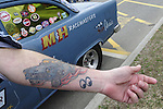 ALEX RECINE, of West Babylon, shows tattoo on his left arm of his 1955 Chevrolet sedan, a Gasser A/Gas class racing car, seen behind arm, at the 58th Annual Easter Sunday Vintage Car Parade and Show sponsored by the Garden City Chamber of Commerce. Hundreds of authentic old motorcars, 1898-1988, including antiques, classic, and special interest participated in the parade.