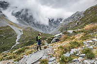 Tramper in Copland Valley admiring mountains, Westland National Park, West Coast, World Heritage Area, South Westland, New Zealand