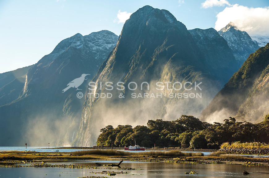 Mist rising from Bowen Falls catches late afternoon sunlight below The Lion at Milford Sound, Fiordland National Park, South Island New Zealand - stock photo, canvas, fine art print