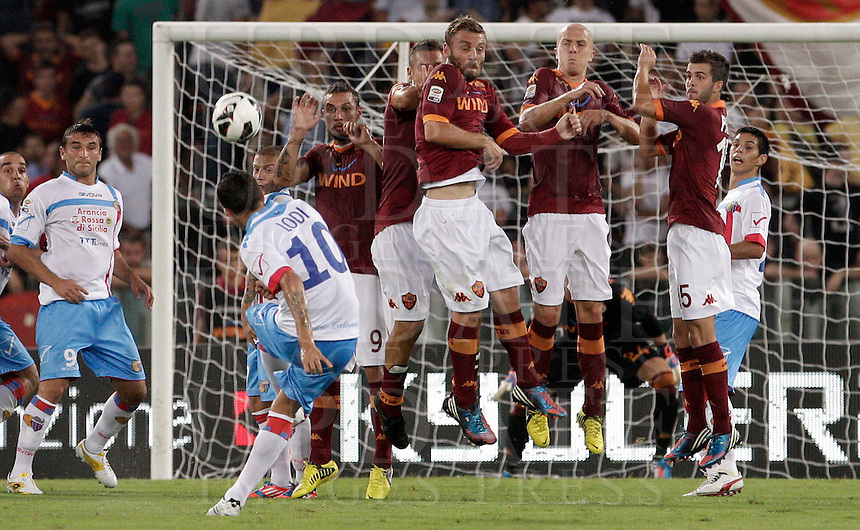 Calcio, Serie A: Roma-Catania. Roma, stadio Olimpico, 26 agosto 2012..Catania midfielder Francesco Lodi, back to camera, kicks a free kick as AS Roma players lined up in a wall, from left in red jersey, Pablo Daniel Osvaldo, Francesco Totti, Daniele De Rossi, Michael Bradley and Miralem Pjanic jump to stop the ball during the Italian Serie A football match between AS Roma and Catania, at Rome, Olympic stadium, 26 August 2012. .UPDATE IMAGES PRESS/Riccardo De Luca