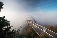 Fog engulfs the 360 Bridge during sunrise on a cold winter's morning on Lake Austin, Texas