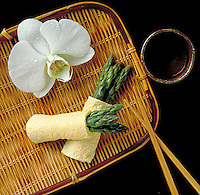 Prepared dish of asparagus eggrolls on a wicker tray with chop sticks, orchid and sake.