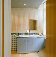 The walls, ceiling and furniture in this bathroom are handpainted with star motifs and geometric patterns