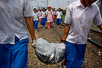 Kartini Emergency School students carry a bag full of catfish bought by the 'Twin Teachers' to be farmed at a pond next to the railway tracks nearby the school. When it's time to harvest, the catfish will be cooked for students' meals. Since the early 1990s, twin sisters Sri Rosyati (known as Rossy) and Sri Irianingsih (known as Rian) have used their family inheritance to set up and run 64 schools in different parts of Indonesia, providing primary education combined with practical skills to some of the country's most deprived children.