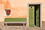 House in the town of Stampa, Switzerland with a green door and a stone bench; Swiss valley town of Stampa where Swiss sculptor Alberto Giacometti was born in the Graubunden Canton of Switzerland