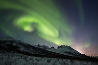 The aurora borealis swirls over Mount Snowden n the Brooks Range mountains, Arctic, Alaska.