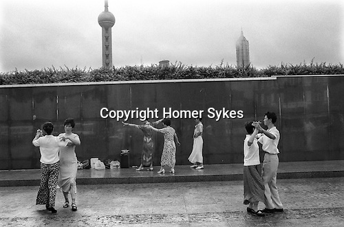 An early morning ballroom dance class on the Bund against the backdrop of the Oriental Pearl TV tower and the Jin Mao building. Ballroom dancing became popular during the 1980s and is either a form of exercise or a competitive sport, not the social activity ir was originally. Shanghai. The Peoples Republic of China. 2000.