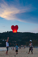 Father and son let the sky lantern go in Phuket beach, Thailand