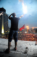 A protestor lights a flare to the delight of a cheering crowd in Taksim Square, Tuesday, June 4, 2013, in Istanbul, Turkey. (Seamus Travers/pressphotointl.com)