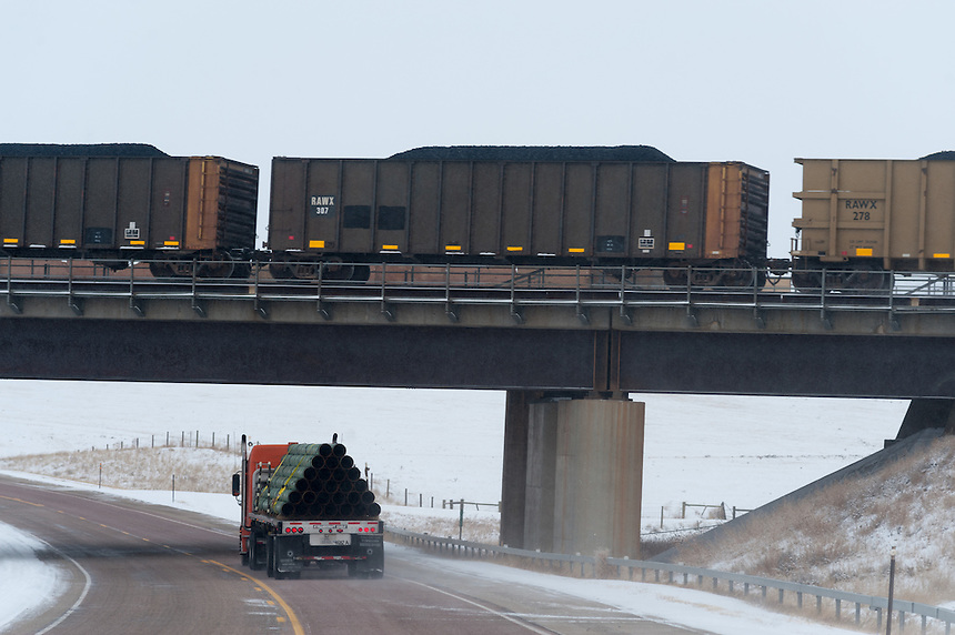 """A pipeline truck passes under a coal train on the energy-rich Powder River Basin near Douglas, Wyo., Thursday, November 22, 2013. The state will require pre-drilling testing of groundwater at sites where hydraulic fracturing, also known as """"fracking"""" is used. (Kevin Moloney for the New York Times)"""