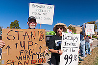 Steve (left) and Susan (right) hold signs at the Occupy Orange County, Irvine camp on November 5.