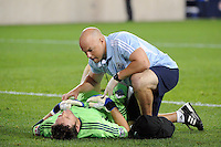 A Vancouver Whitecaps trainer checks the ribs on Vancouver Whitecaps goalkeeper Joe Cannon (1). The New York Red Bulls  and the Vancouver Whitecaps played to a 1-1 tie during a Major League Soccer (MLS) match at Red Bull Arena in Harrison, NJ, on September 10, 2011.