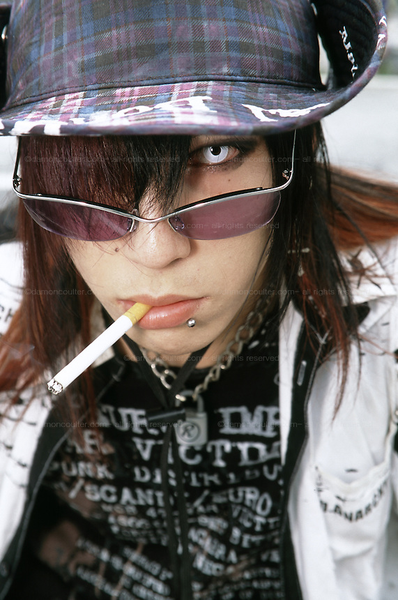 young cosplayer boy smoking a cigarette and wearing sunglasses and