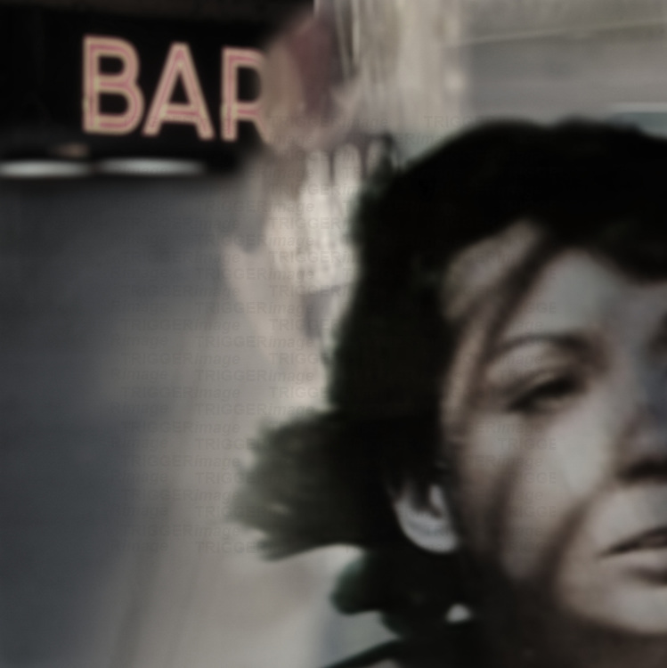 woman with shadows across her face leaving a bar