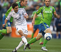 Vancouver Whitecaps FC  forward Shea Salinas takes a shot on goal and Seattle Sounders FC defenders Tyson Wahl, defend during play at Qwest Field in Seattle Saturday June 11, 2011. The game ended in a 2-2 draw.