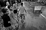Fisherfolk in the Basilan Island community of Maluso make their along a rainy street past a sign warning people entering the village of the local ban on carrying firearms on Jan. 13, 2007. The island is the home to many violently rival political figures as well as being the sometime home of the Islamist terrorist group Abu Sayyaf.