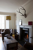 A well worn leather armchair next to fhre fireplace with a lit fire in the sitting room in Whitehouse, a guest house in Chillington, Devon