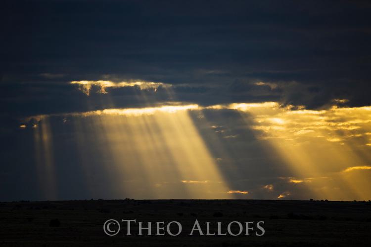 Australia, South Australia;  sun rays filtering through storm clouds in Sturt Stony Desert at Sunset