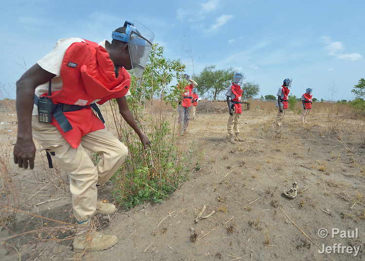 John Simba, a member of an ACT Alliance team, searches for unexploded ordnance in a civilian area near the South Sudan town of Bor, which has been the scene of heavy fighting between government troops and rebels since a dispute within the ruling party turned violent in December 2013 and quickly ripped the newly independent nation along ethnic and tribal lines. The explosive ordnance disposal team is part of the humanitarian mine action program of Dan Church Aid, a member of the ACT Alliance. The program also deploys mine risk education teams to help villagers identify and understand the dangers of unexploded ordnance and land mines from this most recent conflict as well as ordnance left over from decades of civil war.