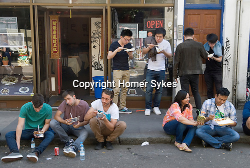 Brick Lane Tower Hamlets people eating Chinese food. London E1 UK