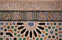 Detail of tiles with geometric and interlacing designs in the Mexuar, meeting room for Council of Ministers and public reception room of the Sultan, Alhambra, Granada, Andalusia, Southern Spain. Above the tiles is cursive Arabic script carved in stucco. The Alhambra was begun in the 11th century as a castle, and in the 13th and 14th centuries served as the royal palace of the Nasrid sultans. The huge complex contains the Alcazaba, Nasrid palaces, gardens and Generalife. Granada was listed as a UNESCO World Heritage Site in 1984. Picture by Manuel Cohen
