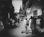 Tibetan style spire of Jama Masjid (Mosque) hints at a Bud dhist past.  Meanwhile locals shop in the labyrinth of the old city of Srinagar, Indian Administered Kashmir.