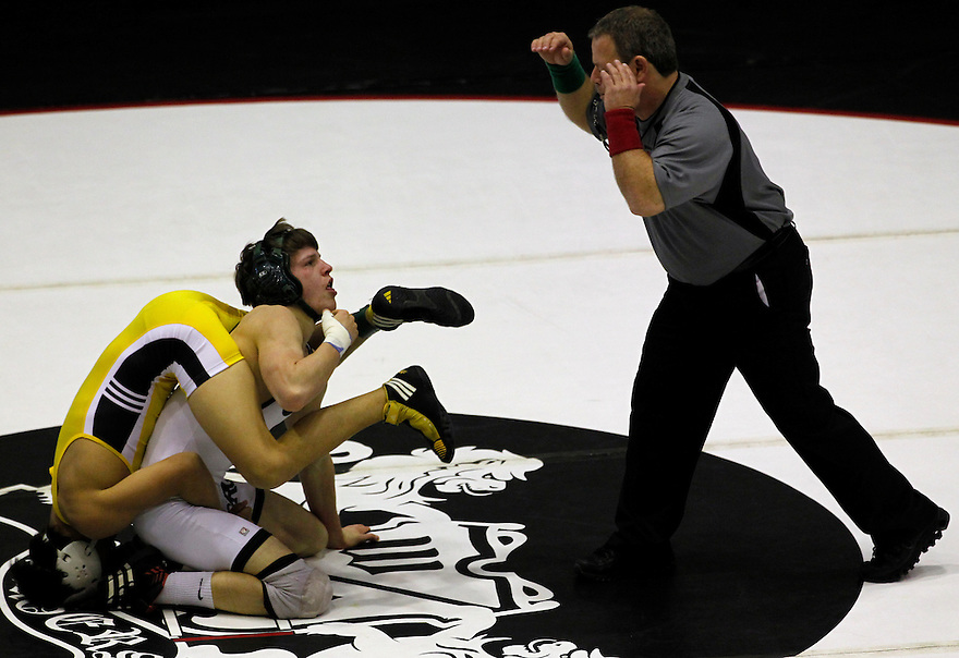 Trent Cooper of Reagan High School (white) gets wrapped up against Rowe High School's David Diaz during the boys' finals of the Region IV wrestling tournament at Littleton Gymnasium on Saturday, Feb. 11, 2012. Cooper won the 132 lb weight class.