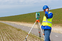 Engineer working with a modern theodolite or total station on a tripod