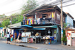 Traditional Thai two story shop house and living space butts up against a new building in the Thewet Market area of Old Bangkok, Thailand.