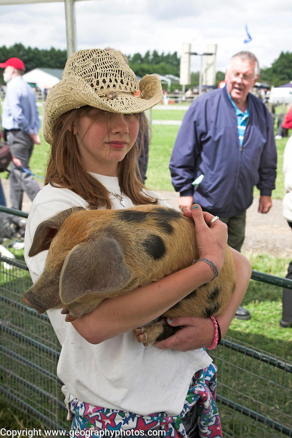 Girl holding an Oxford Sandy Black Piglet at Suffolk Smallholders annual show, Stonham Barns, Suffolk, England, July 2008