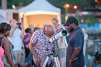 Hundreds of visitors to the World Science Festival participate in a stargazing event in Brooklyn Bridge Park in New York on Saturday evening, June 1, 2013. Amateur and professional astronomers brought out their telescopes for the public to scan the heavens and view astronomical features in the event which is just part of the week-long festival. (© Richard B. Levine)